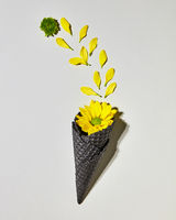 Ice cream bouquet in wafer cone with yellow flower on gray background, flat lay
