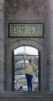 Female tourist taking a selfie photo in front of one of the entrances of the Blue Mosque, Istanbul, Turkey