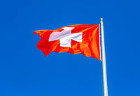Flag of Switzerland flying in the wind against the sky