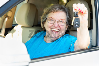 Happy Senior Woman Sitting In New Car Holding The Keys