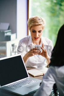 Beautiful businesswoman is typing on her smartphone