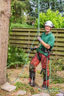 Dutch arborist with climbing equipment in garden