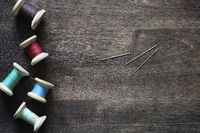 Sewing thread on a wooden background. Set of threads on bobbins