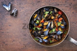 Traditional barbecue Italian blue mussel in red wine sauce as top view in a casserole with copy space
