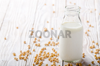 Non-dairy alternative Soy milk or yogurt in glass bottle on white wooden table with soybeans aside