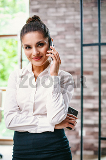 Successful woman is talking on a smartphone.