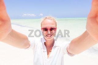 Young woman wearing white beach tunic taking selfie on tropical white sandy beach.