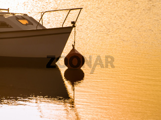 Boats on a lake at sunset, moored with a buoy and calm water in the reservoir of La Maya (Salamanca)