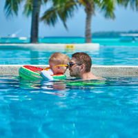 Toddler boy in resort pool with father