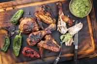 Traditional Caribbean barbecue chicken wings and drumsticks with chimichurri sauce