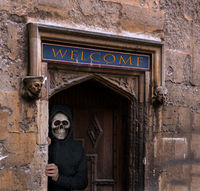 Halloween theme of man with skull mask welcoming to haunted house