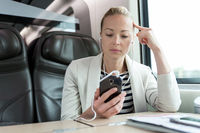 Businesswoman communicating on mobile phone while traveling by train.