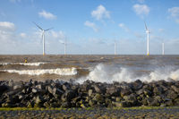 Dutch sea with off shore wind turbines and breaking waves
