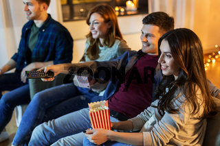 friends with popcorn watching tv at home