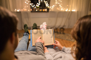 close up of couple reading book at home