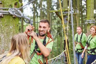 Junge Leute helfen sich im Kletterkurs