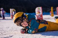 little snowboarder lying on the snow