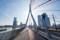 Erasmus bridge against blue sky and sun in Rotterdam Netherlands
