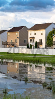 Vertical frame Homes and cloudy sky reflected on the shiny surface of a grassy pond
