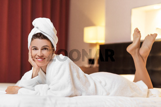 Young woman in bathrobe lying in hotel room, relaxed after taking a bath