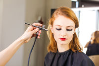 Visagiste making the girl professional makeup using an airbrush.