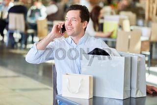 Mann beim Shopping telefoniert mit Handy
