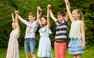 happy kids holding raised hands in summer park