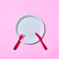 Dining set served fork and knife on pink.