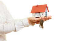 Haus mit Schlüssel auf Hand als Hausbau oder Hauskauf Konzept