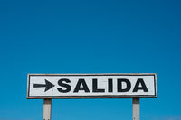 Exit sign (spanish: SALIDA) isolated on blue sky -