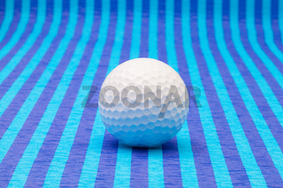White golf ball on blue striped table.