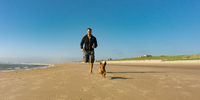 Man with his little cute dog running at the beach