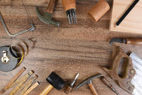 High angle closeup of a large group of tools arranged on a wood workbench around a blank space in the middle