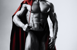 Male bodybuilder puts on his shoulders a red cloak with a serious face