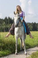 Junge Frau im Dirndl reitet auf Araberstute