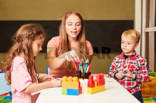 Erzieherin und Kinder malen zusammen