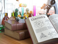 Chemistry education concept. Open books with text chemistry and formulas and textbooks, flasks with liquids and microscope in a classroom or a laboratory.