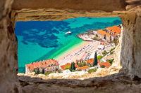 Banje beach in Dubrovnik aerial view through stone window