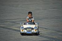 Junge fährt in einem elektrisch betriebenen Spielzeugauto, Ulanbator, Mongolei