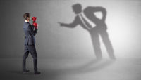 Businessman fighting with his bossy shadow