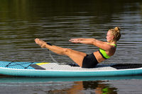 Active woman in yoga pose on SUP