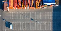 Ukraine, Kyiv. April 08, 2018: Aerial view, from the drone to the warehouse with a lot of different building materials and parking with a truck sunny day. Top view.