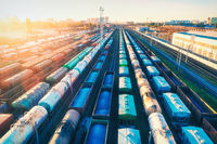 Aerial view of colorful freight trains at sunset. Cargo wagons