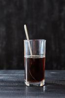 A transparent glass with coffee and a spoon on a black wooden background with copy space.
