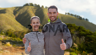 smiling couple in sport clothes showing thumbs up