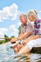 Senioren Paar beim Angeln am See im Sommer