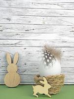 Ostern Hintergrund mit Osterei und Osterhasen auf grün vor Holz