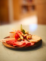 Mix of traditional spanish ham salami, parma ham on grissini bread sticks, marinated vegetables and olives on wooden plate with rustic decor