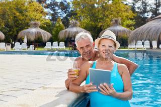 Senioren Paar mit Tablet im Hotel Pool