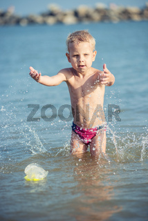 Cute little kid wearing mask and flippers for diving at sand tropical beach.